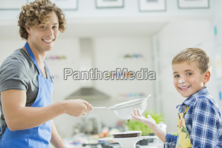 father and son baking in kitchen