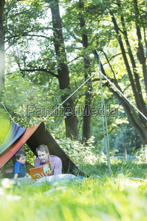 father and son reading in camping