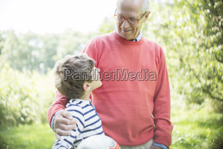grandfather and grandson hugging outdoors