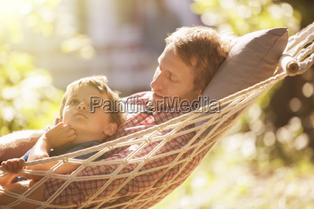 father and son relaxing in hammock