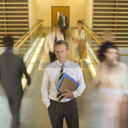 businessman standing in busy office corridor