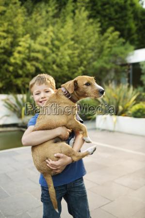 smiling boy holding dog outdoors