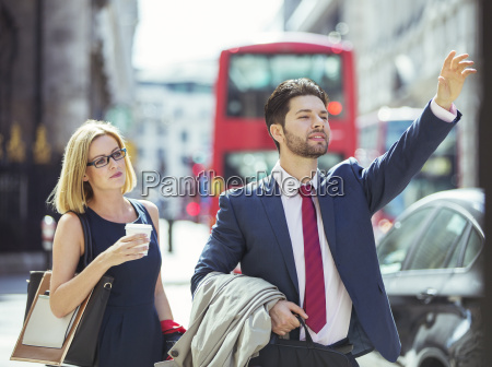 business people hailing taxi in city