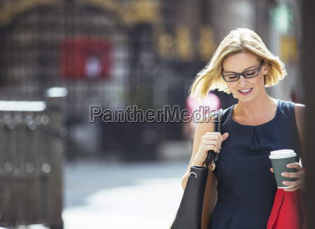 businesswoman carrying cup of coffee in