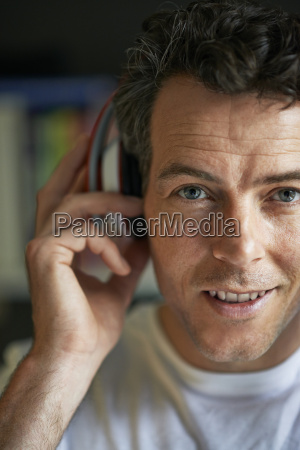 smiling man with headphones on close