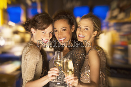 smiling women toasting champagne glasses in