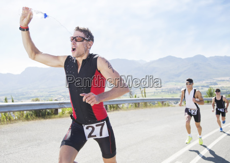 runner spraying himself with water in