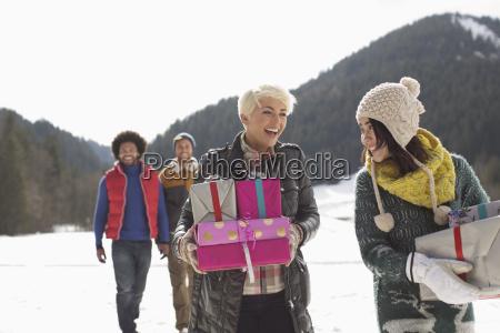 freunde mit weihnachtsgeschenken im schnee