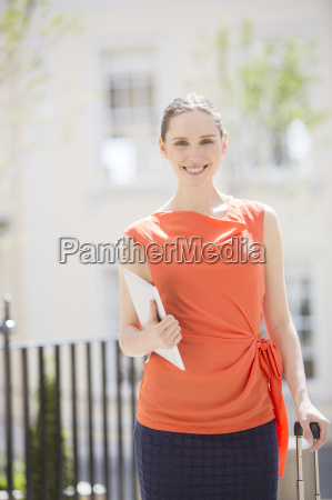 businesswoman carrying digital tablet on city