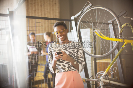 smiling businesswoman texting on cell phone