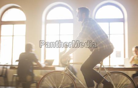 casual geschaeftsmann fahrradfahren im sonnigen buero