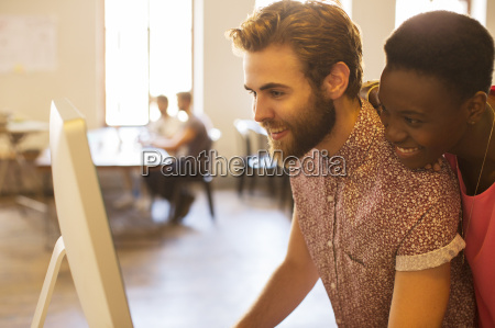 smiling casual business people sharing computer