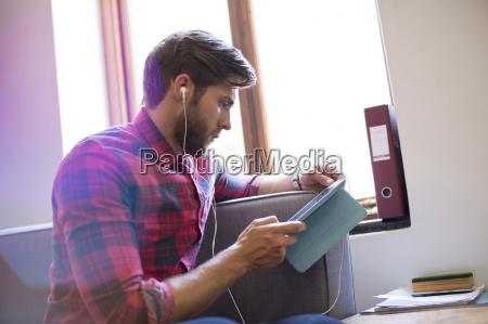 casual geschaeftsmann mit kopfhoerer und digitale