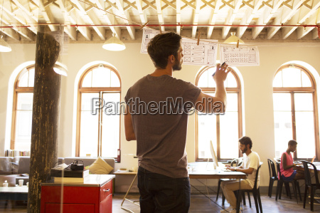 casual businessman reviewing hanging diagrams in
