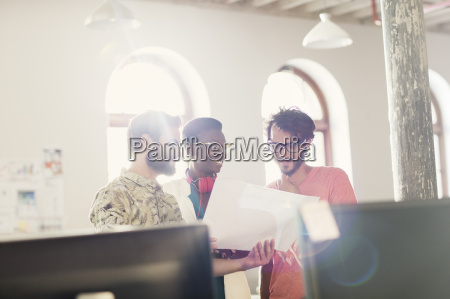 creative business people reviewing paperwork in