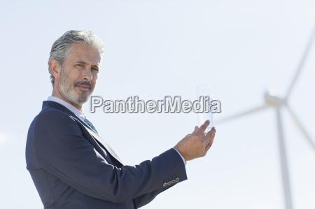 geschaeftsmann mit glas wasser von windkraftanlage