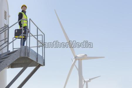 arbeiter steht auf windkraftanlage in laendlicher