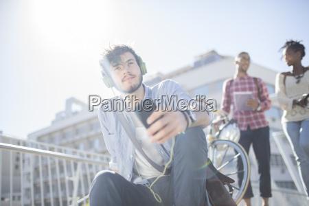 man listening to headphones on city