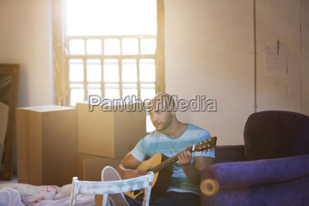 man playing guitar in new home