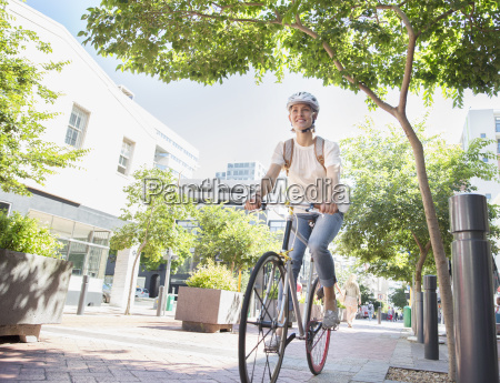smiling young woman with helmet riding