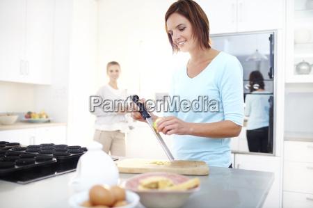 woman zesting lemon in kitchen