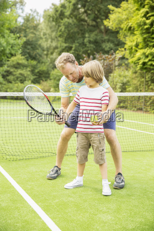 father teaching son to play tennis