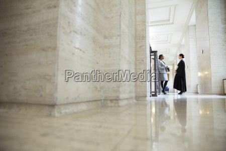 lawyer and judge talking in hallway
