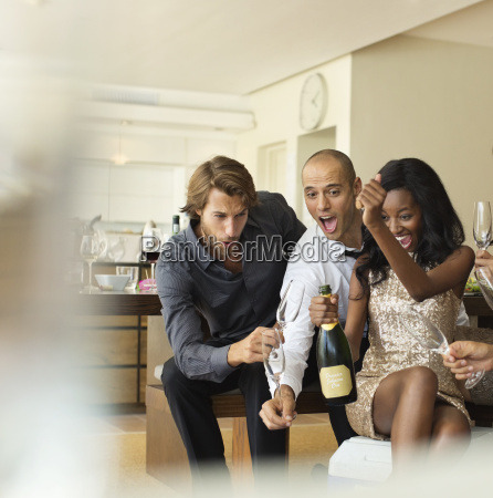 friends opening bottle of champagne together