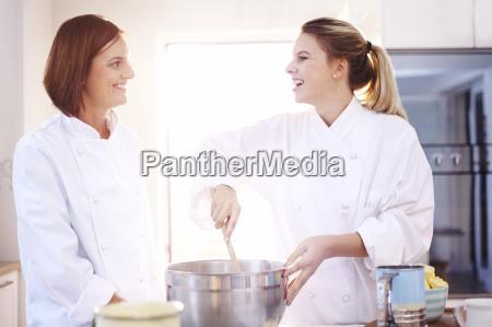 smiling chefs baking in kitchen