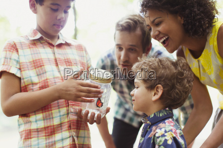 family watching butterfly in jar