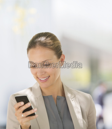 businesswoman texting with cell phone outdoors