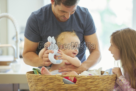 father and children sorting laundry