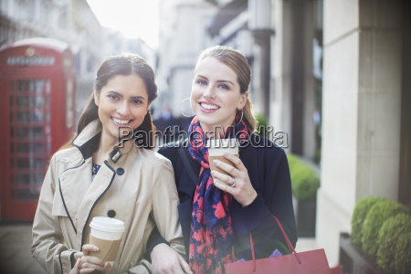 women drinking coffee together down city