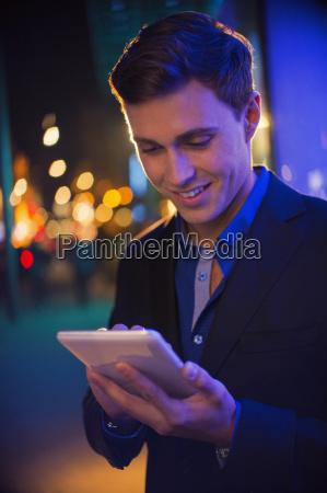 man using digital tablet on city