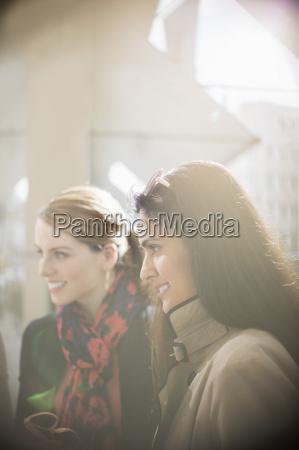 women smiling on city street