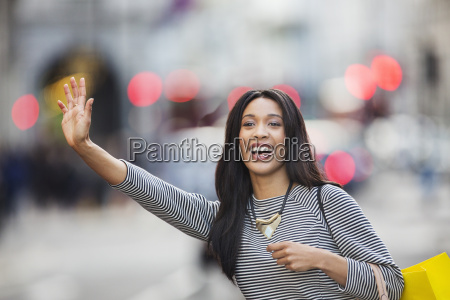 woman waving for taxi on city