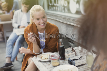 smiling blonde woman eating dessert at