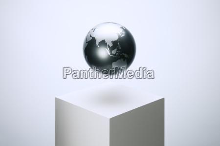 globe schwebt ueber podest