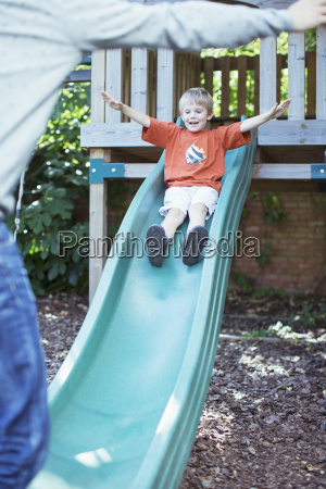 father catching son on slide