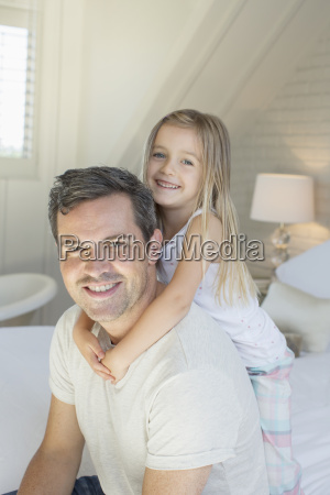 father and daughter hugging on bed