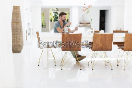 man using digital tablet at breakfast