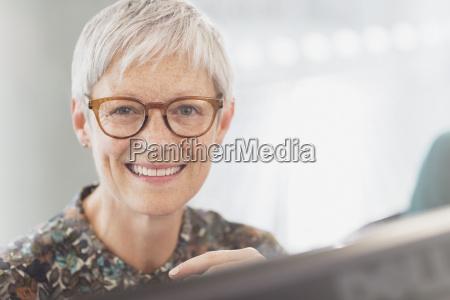 portrait smiling senior businesswoman with eyeglasses