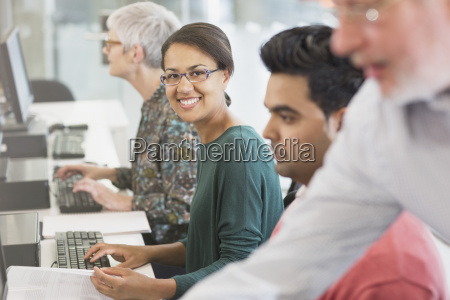 portrait smiling woman at computer in
