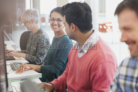 smiling students talking at computers in