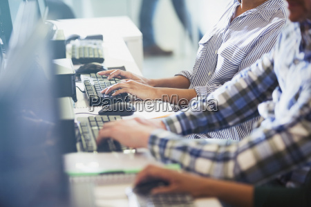 students typing at computers in adult