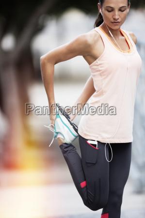 woman stretching legs on city street