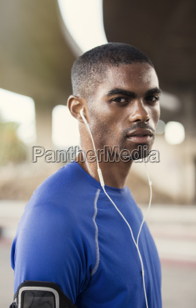 man with headphones exercising on city