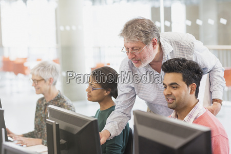 professor helping student at computer in