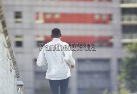 man running through city street