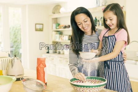 mother and daughter baking sifting flour